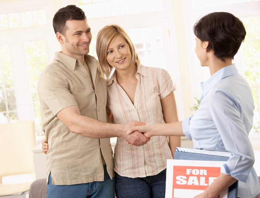 Estate agent congratulating young couple on making deal on new h